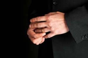 close up of mature man's hands removing wedding ring